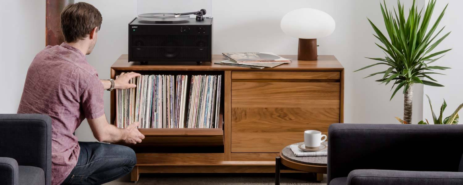 AERO Modern Walnut LP Storage Cabinet with Modern tabletop record player and 100+ LP swivel bin storage in a living room setting.